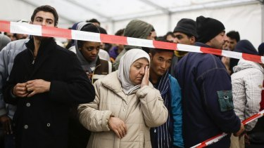 Migrants wait in exclusion zone for transport to a registration office at the State Office of Health and Welfare in Berlin, Germany.