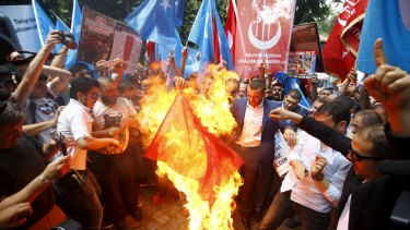 Demonstrators set fire to a Chinese flag during a protest near China's consulate in Istanbul this week.