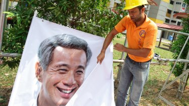 Workers prepare a People's Action Party (PAP) banner earlier this month.