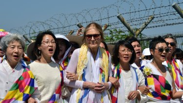US feminist Gloria Steinem (centre) and South Korean peace activists march along a military fence at a checkpoint in Paju.