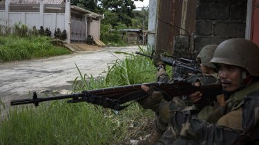 Soldiers take positions while evading sniper fire in Marawi.
