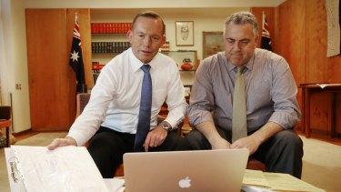 Prime Minister Tony Abbott poses with Treasurer Joe Hockey as they look through the 2015 budget.