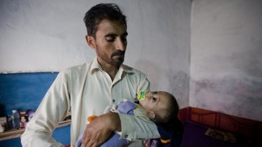 Eight-month-old Sufiyan Qadir carried by his father Noor Qadir, 33, at his house in the city of Peshawar. Qadir has no doubt Peshawar's rats are turning into killers.