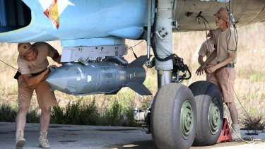 Russian military support crew attach a satellite-guided bomb to a jet fighter in Syria on Saturday.