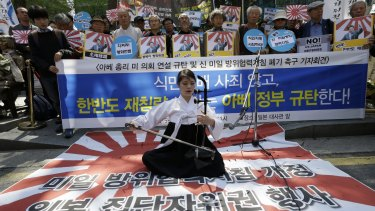 South Korean university student Lee Ye-in performs on a Japanese rising sun flag in Seoul during a rally to denounce Japanese Prime Minister Shinzo Abe's address to a joint session of the US Congress.