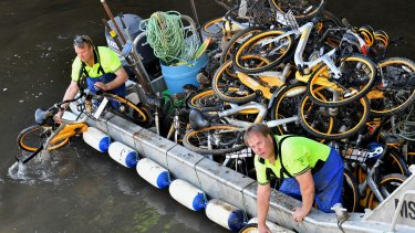 Contractors collect oBikes from the Yarra River in Melbourne.