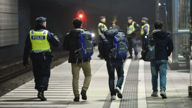 Swedish police escort three men from a train at Hyllie station outside Malmo. Sweden was looking to deport between 60,000 and 80,000 asylum seekers in coming years.
