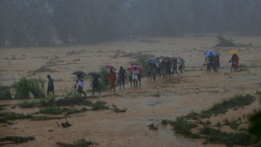 Sri Lankans walk towards safety during after heavy rain in Elangipitiya village.