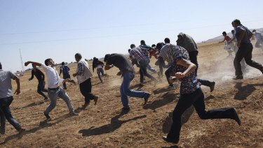 Kurdish protesters at the border with Syria flee from Turkish teargas after trying to watch the fighting in the border town of Kobane in October 2014.