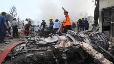 Firefighters and military personnel work at the site.