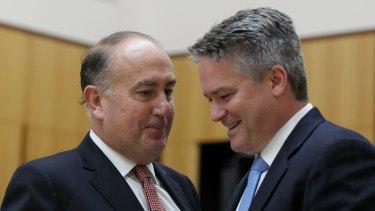 Secretary of Treasury John Fraser confers with Finance Minister Mathias Cormann.
