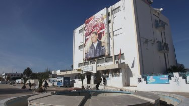 """The post office building next to Sidi Bouzid's provincial government building is decorated with a giant poster of Mohamed Bouazizi, """"the symbol of national unity""""."""