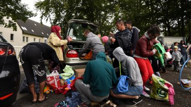 Refugees sift through donated clothing at a refugee camp near Hilbersdorf, Germany.