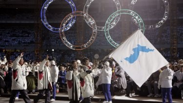 A unification flag is carried into the stadium during the 2006 Winter Olympics in Turin, Italy.