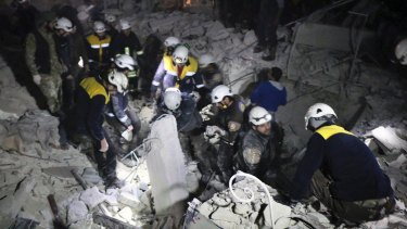 Syrian White Helmets workers inspect the damage after a bombing that targeted the office of Ajnad al-Koukaz, a militant group consisting of foreign fighters mostly from the Caucuses and Russia, in Idlib, Syria, on Sunday.