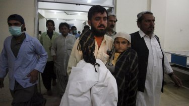 Relatives carry a boy who survived the attack into a hospital in Quetta, Pakistan.