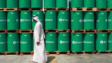 A visitor passes ENOC-branded oil barrels stored at the Emirates National Oil Co.