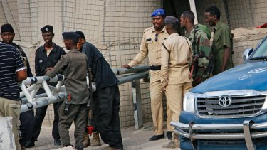 Somali police guard the road leading to the scene of the suicide bomb attack.