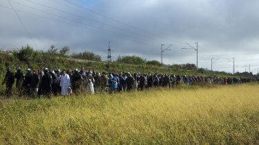 Refugees walk towards a reception facility after crossing into Slovenia from Croatia.
