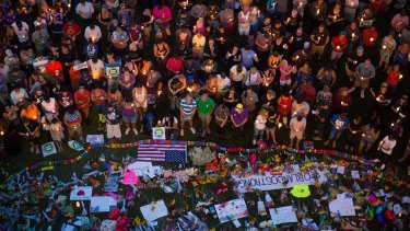 Mourners attend a candlelight vigil in Orlando the day after an attack on a gay nightclub left at least 50 people dead.