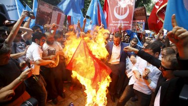 Demonstrators set fire to a Chinese flag during a protest against China near the Chinese consulate in Istanbul, Turkey, in July.