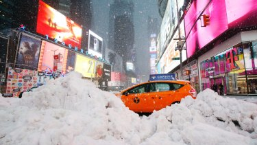A taxi drives past piles of snow as a storm sweeps through Times Square on Tuesday.