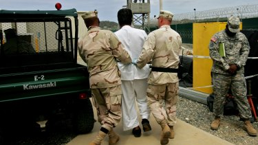 A Guantanamo detainee escorted by US military personnel on the grounds of the Guantanamo Bay naval base in 2007.