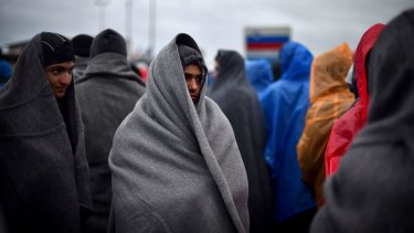 Refugees attempt to keep warm as they wait in the rain at the Trnovec border crossing.