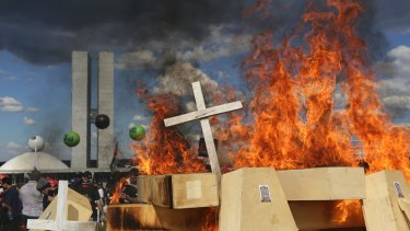 Striking police officers set fire to coffins during a protest against pension reforms outside Congress in Brasilia, on Tuesday.