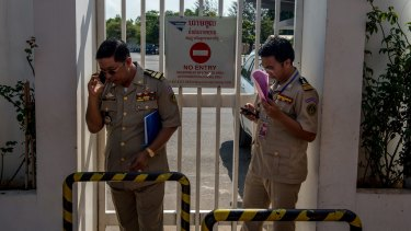 Security guards at Phnom Penh airport on Thursday. waiting for the refugees to land.