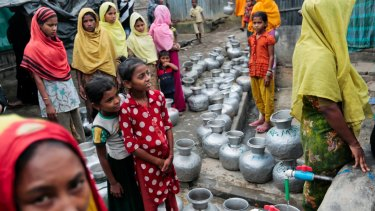 Rohingya women and children wait in a queue to collect water at the Leda camp, an unregistered camp for Rohingya in Teknaf, 296 kilometers south of Dhaka, Bangladesh.