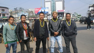 Naga men wearing yellow necklaces, a symbol of the Angami tribe, wait to block government vehicles in the streets of Kohima.