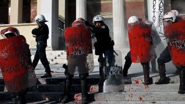 Riot police splattered with red paint thrown by protesters in Athens on Thursday.