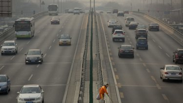 A road worker picks up trash along the median of a highway on a smoggy day in Beijing earlier this year.