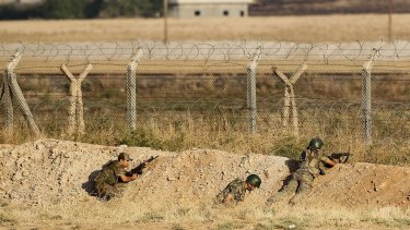 Turkish soldiers take position in June at the Syrian border fence, near the Turkish border town of Akcakale.