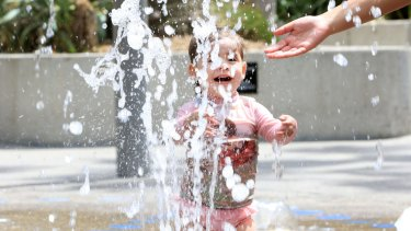 Anika, 2, plays in the water feature in Tumbalong Park, Darling Harbour.