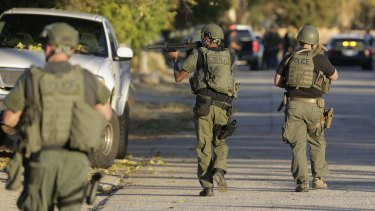 Police officers search for a suspect in a mass shooting in San Bernardino, California on Wednesday.
