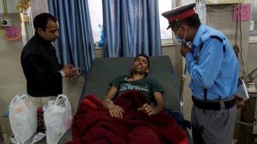 Rishi Khanal speaks to a security guard at a hospital in Kathmandu.