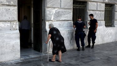 A pensioner arrives to receive part of her pension as police officers stand by at a National Bank branch in Athens on Tuesday.