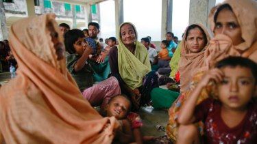 Members of Myanmar's Muslim Rohingya minority sit in a temporary shelter at Shah Porir Deep.