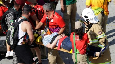 An injured woman is taken away after being struck by an overhead television camera that fell from wires suspending it over Olympic Park in Rio on Monday.