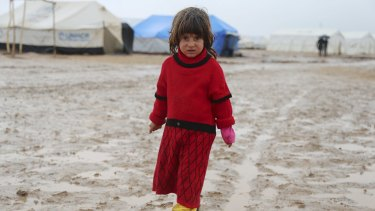Treated like chattel by Islamic State ... A refugee girl from the minority Yazidi sect stands on a muddy path outside tents during wintry weather at Nowruz refugee camp in Qamishli, northeastern Syria.