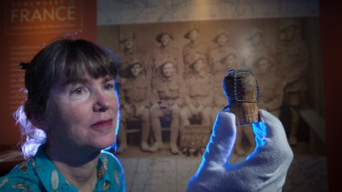 """Curator Jenny Long at the """"Somewhere In France"""" exhibition with a Moët & Chandon champagne cork from 1918, collected by Signaller Ray Jones."""