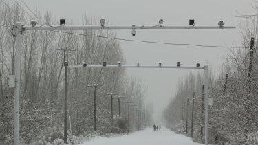Surveillance cameras keep watch on a road in Akto County, Xinjiang.