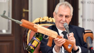 "Czech President Milos Zeman holds a mock submachine gun inscribed with the words ""At journalists"", and a bottle of Becherovka liquor instead of the gunstock, in October last year."