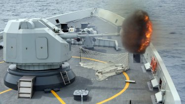 """An anti-surface gun is fired from China's Navy missile frigate Yulin during """"Exercise Maritime Co-operation 2015""""."""