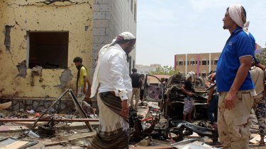 Fighters loyal to the government gather at the site of a suicide car bombing in Yemen's southern city of Aden in August.