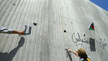 Foreign activists spray graffiti on the wall erected by Israel near the northern West Bank town of Qalqilya, which is also walled off on three sides.