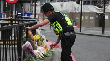 A police officer lays flowers passed to him by members of the public on the north side of London Bridge.