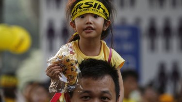 A supporter of pro-democracy group Bersih carries a child on his shoulders during Sunday's protest in Kuala Lumpur.
